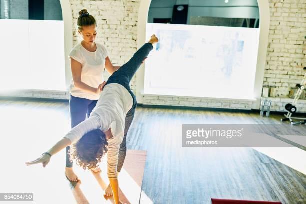 Yoga Lehrer unterstützen Schüler