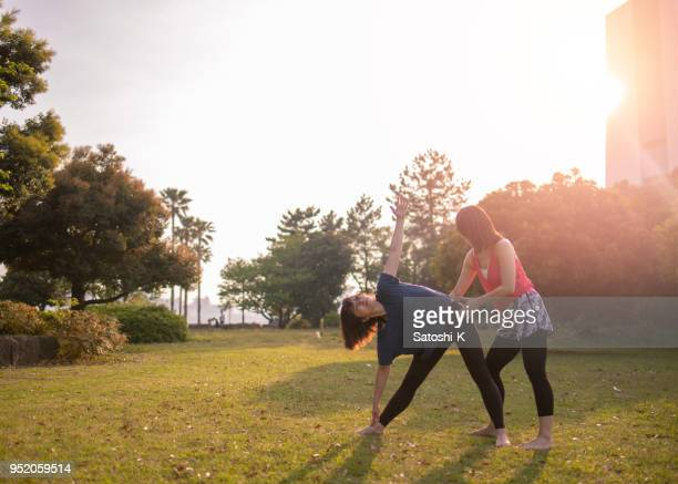 Yoga instructor assisting student
