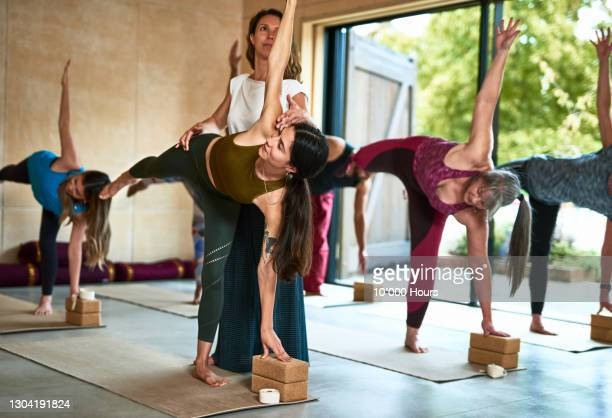 yoga instructor assisting woman in half moon pose in class - human limb stock pictures, royalty-free photos & images