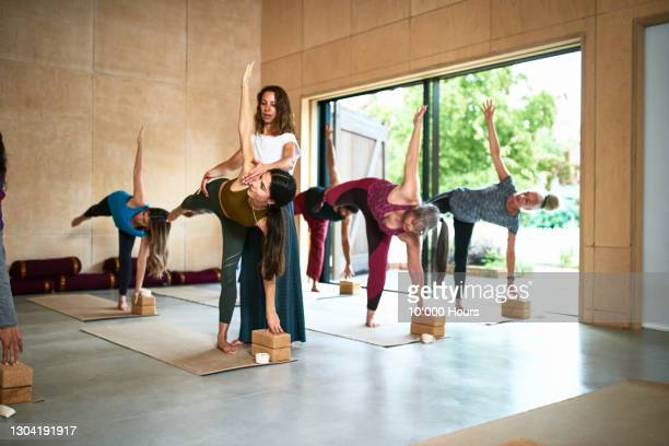 yoga instructor assisting woman in standing pose - human limb stock pictures, royalty-free photos & images