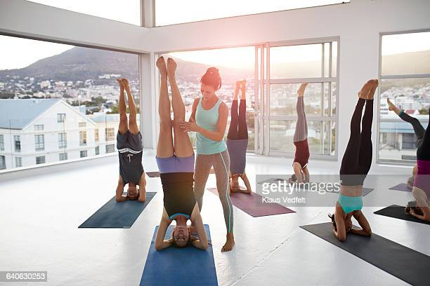 Yoga instructor assisting woman standing on head