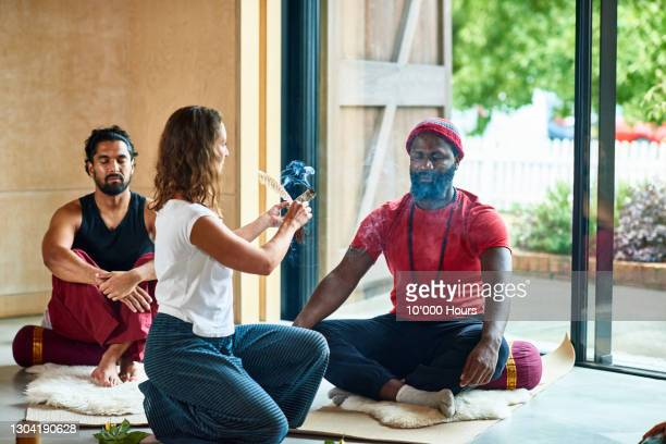 yoga instructor burning smudge stick in smoke cleansing ritual - mid adult men stock pictures, royalty-free photos & images