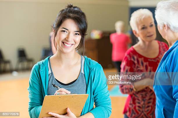 Yoga instructor checks class roster before class