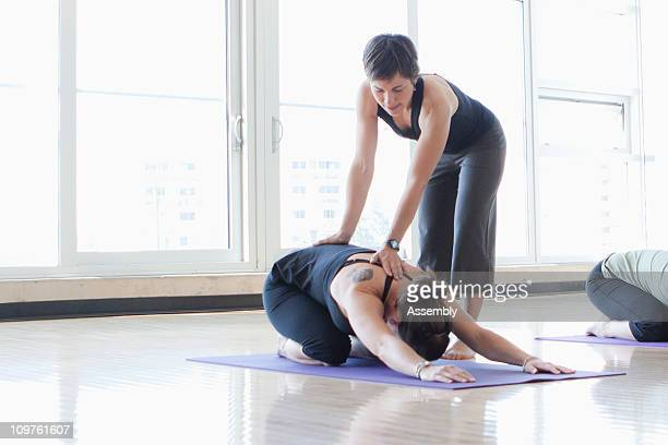 yoga instructor helping students with poses - yoga teacher stock pictures, royalty-free photos & images