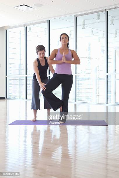 yoga instructor helps woman with pose - tree position stock photos and pictures