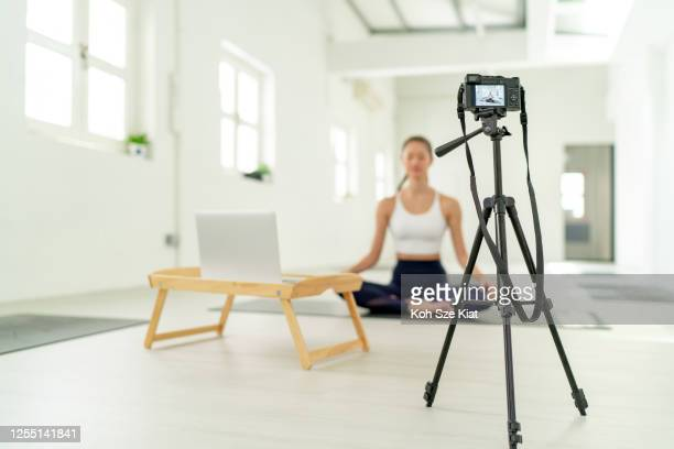 yoga instructor live streams to her students and followers - yoga teacher stock pictures, royalty-free photos & images