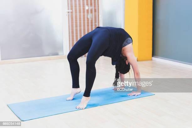 Yoga instructor performing Chakrasana position during her Yoga Class