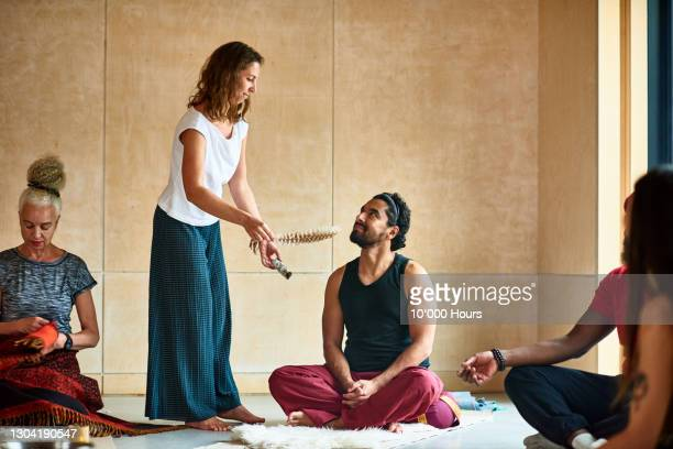 yoga instructor performing smudge stick ceremony - participant stock pictures, royalty-free photos & images