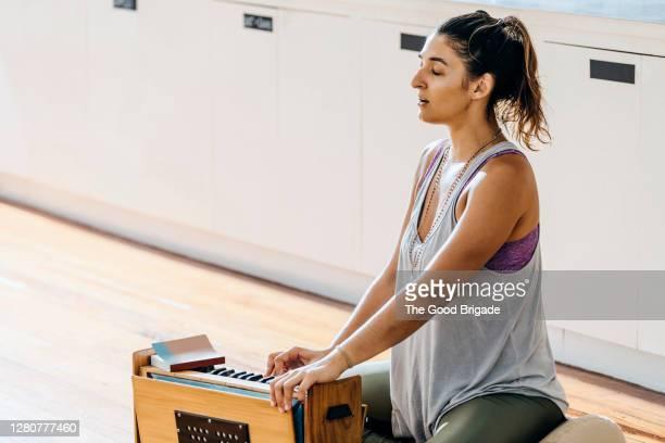 yoga instructor playing harmonium at studio - 詠唱 ストックフォトと画像