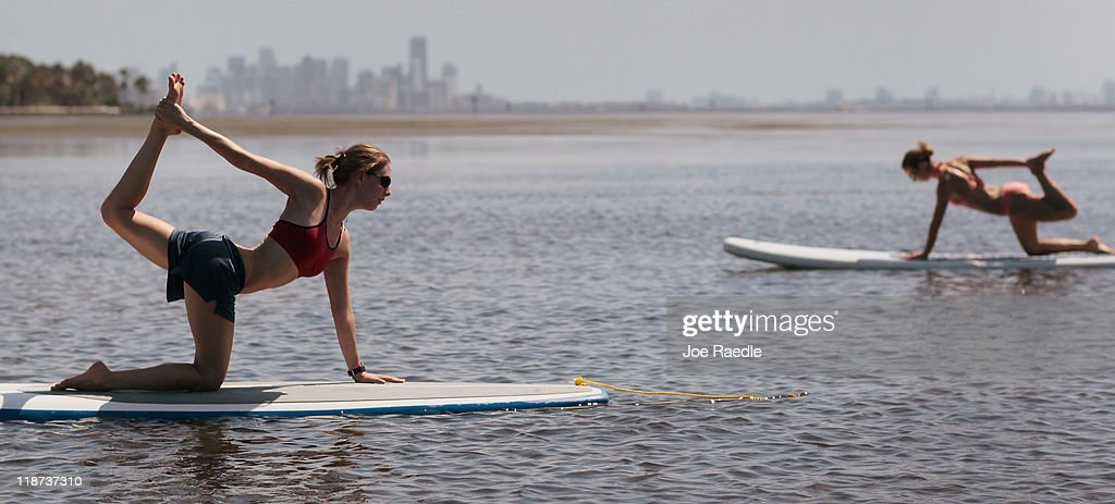 Yoga instructor Sarah Henry leads a class during a paddleboard yoga session at Adventure Sports Miami on July 10, 2011 in Miami, Florida. The paddle board is said to give the body's core more of a workout then in a gym since the platform is unstable and one must use the muscles to remain balanced on the board.