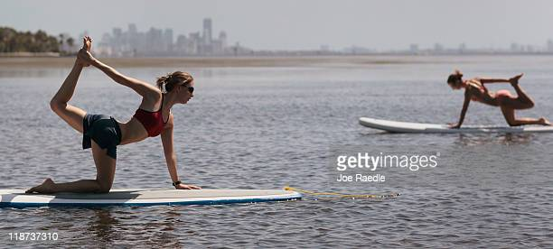 Yoga instructor Sarah Henry leads a class during a paddleboard yoga session at Adventure Sports Miami on July 10 2011 in Miami Florida The paddle...