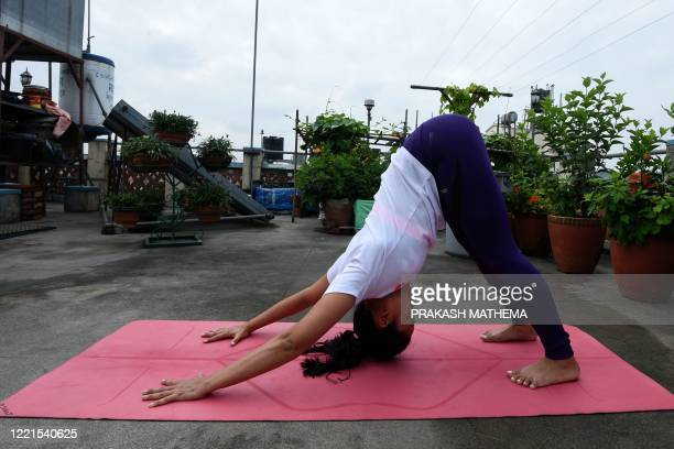 Yoga instructor Suzana Pradhan performs a yoga posture at a rooftop in her house during International Yoga Day, in Kathmandu on June 21, 2020.