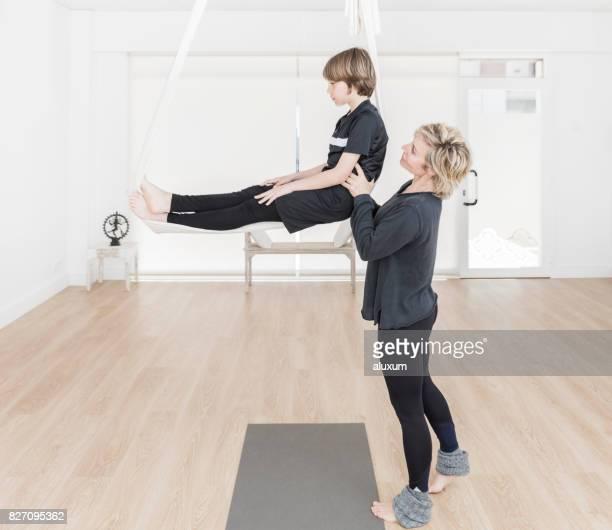 Yoga instructor teaching aerial yoga to child