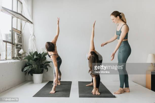 yoga instructor teaching yoga in studio - yoga teacher stock pictures, royalty-free photos & images