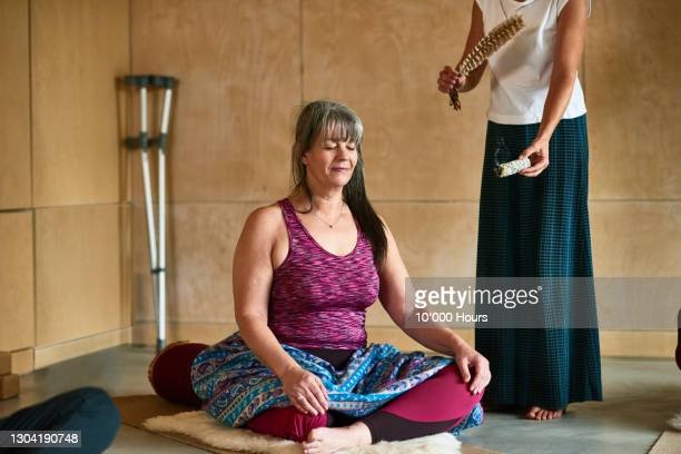 yoga instructor using smudge stick and feather in smoke cleansing ritual - disability stock pictures, royalty-free photos & images