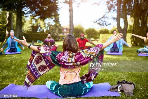yoga instructor with arms out rear view - buddhism stock pictures, royalty-free photos & images