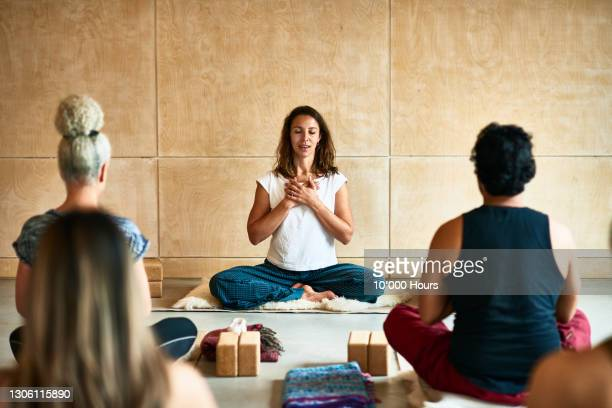 yoga instructor with hands clasped teaching class - teacher stock pictures, royalty-free photos & images