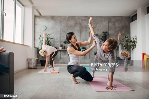 istruttore di yoga con donne anziane in lezione di yoga - solo adulti foto e immagini stock