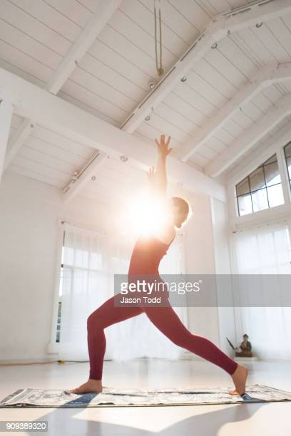 Yoga instructor woman practicing High Crescent Lunge in a yoga studio