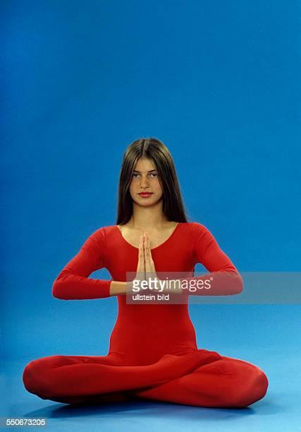 2 Yoga Lotossitz Konzentration gefaltete Hände junges Mädchen roter Gymnastikanzug dunkelblonde Haare undatiert