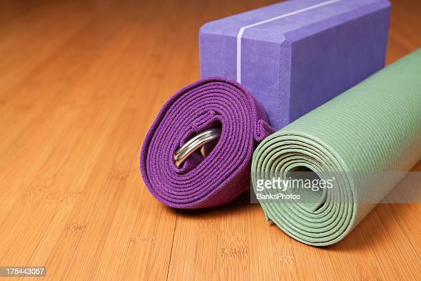 yoga mat, block and strap on studio floor - strap stock photos and pictures