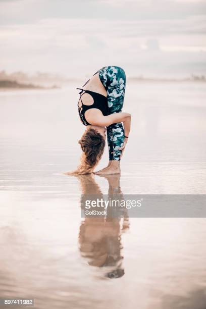 yoga on the beach - beautiful women bent over stock photos and pictures