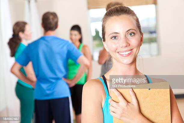 Yoga or fitness instructor holding clipboard in front of class