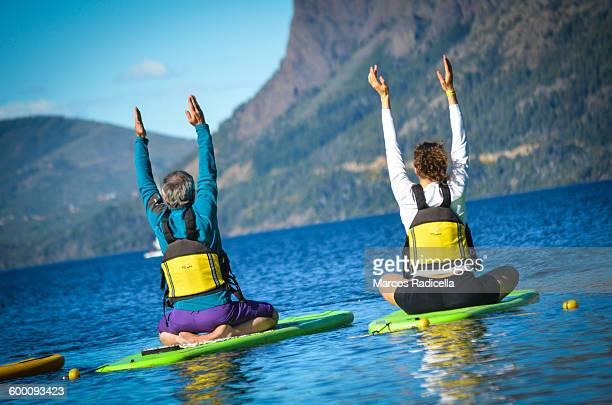 yoga paddleboarding - radicella photos et images de collection