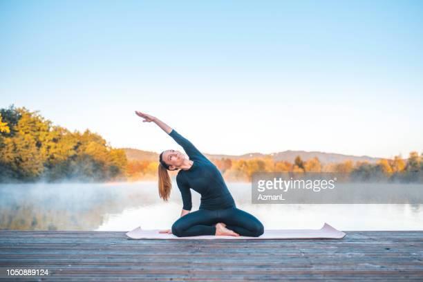 yoga-pose - sitzende seite biegen, pose (parsva sukhasana) - seeufer stock-fotos und bilder