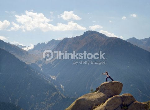 yoga poses on a rock high in the mountains stock photo
