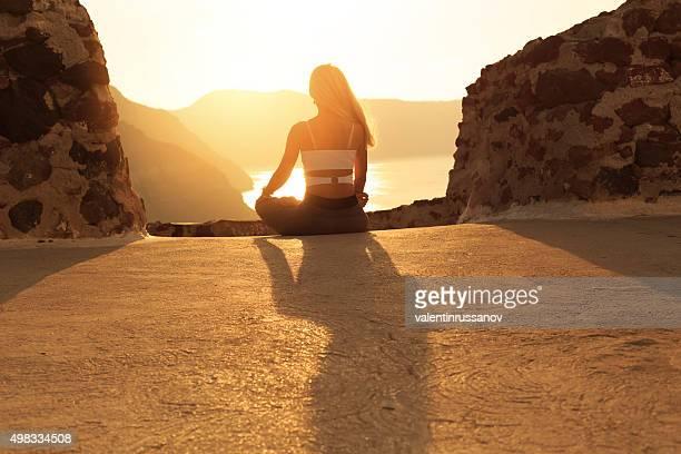 Yoga practice at sunset in Santorini Greece
