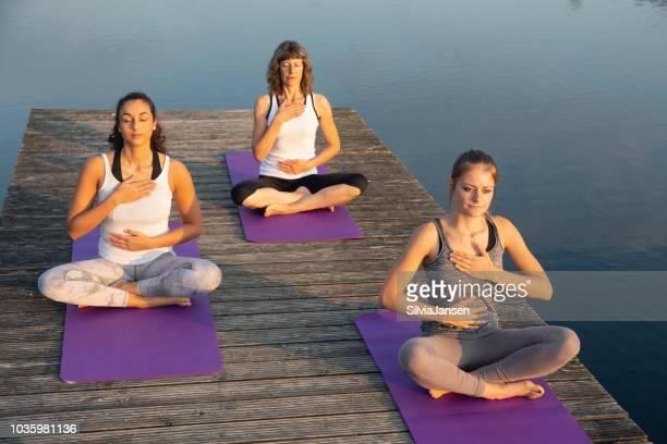 Yoga Entspannungsübung am Steg am See: fühlen den Atem