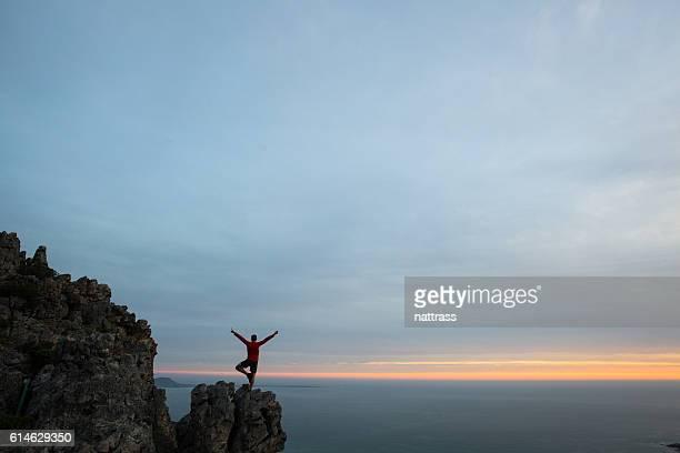 Yoga stance on mountain peak at sunset