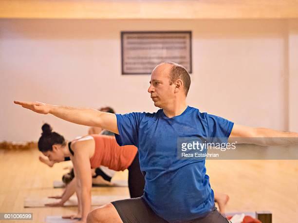 yoga student in virabhadrasana 2 - 半そで ストックフォトと画像