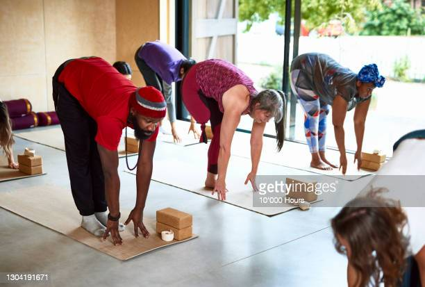 yoga students bending forwards on yoga mats in class - physical disability stock pictures, royalty-free photos & images