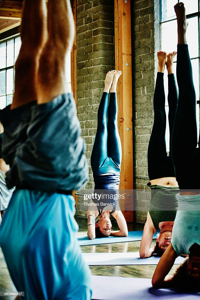 Yoga students doing headstands during class : Stock Photo