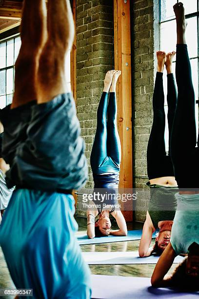 Yoga students doing headstands during class