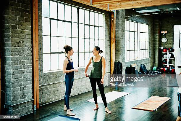 Yoga students in discussion before class in studio