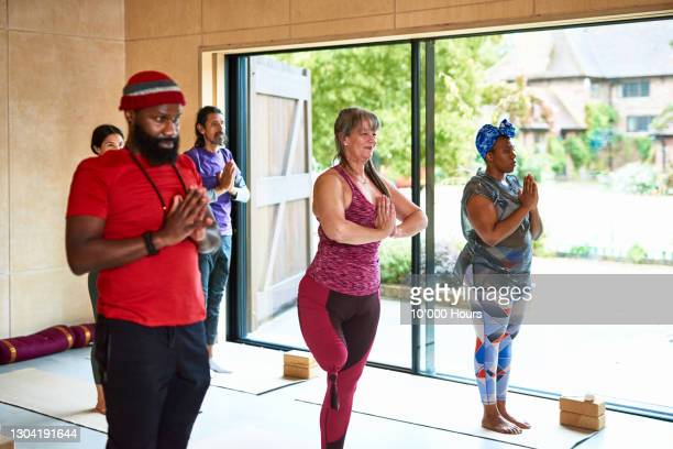 yoga students in mountain pose in studio - vacations stock pictures, royalty-free photos & images