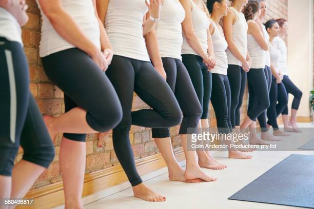 Yoga students leaning on studio wall