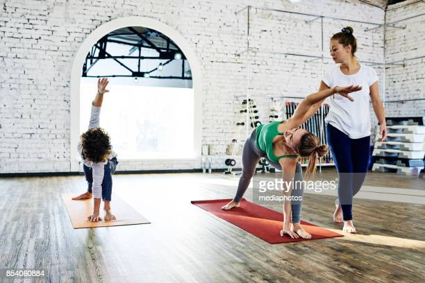 yoga students practicing asana - yoga teacher stock pictures, royalty-free photos & images