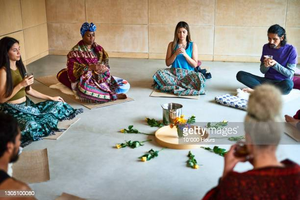 yoga students sitting in circle for traditional tea ceremony - ceremony stock pictures, royalty-free photos & images