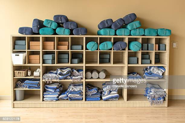 Yoga studio wall with shelf of blocks, bolsters and blankets