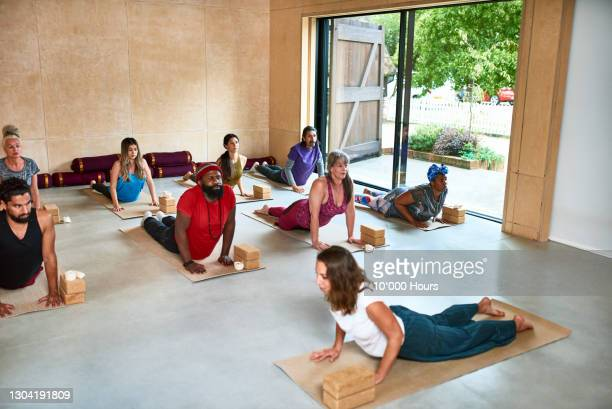 yoga teacher at front of class demonstrating upward facing dog position - mid adult men stock pictures, royalty-free photos & images