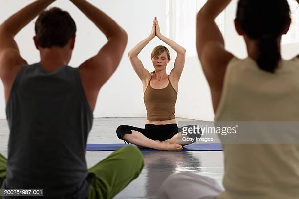 yoga teacher at front of class, hands in prayer position above head - yoga teacher stock pictures, royalty-free photos & images