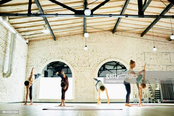 yoga teacher correcting pose of students - yoga teacher stock pictures, royalty-free photos & images
