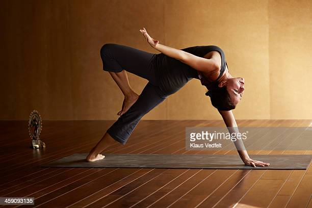 Yoga teacher posing Camatkarasana (Wild Thing)