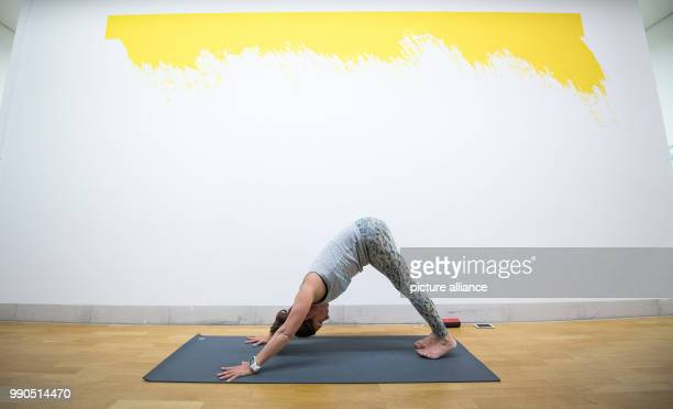 Yoga teacher Roberta Proefrock practices yoga during a yoga course in front of the art work Trevira of Leni Hoffman at the Gallery Stadt Sindelfingen...