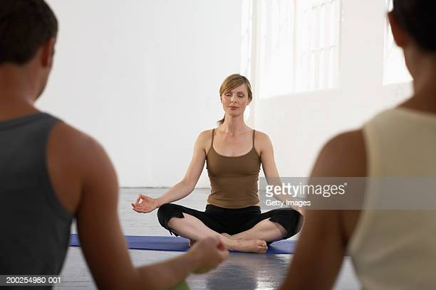yoga teacher sitting in sukhasana at front of class, eyes closed - yoga teacher stock pictures, royalty-free photos & images