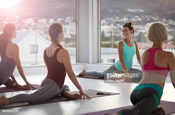 Yoga teacher smiling to students at yoga session
